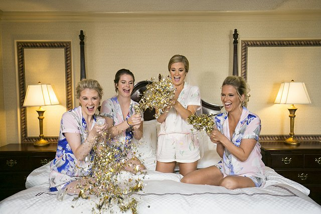 Bridal party posing with confetti party poppers on hotel bed