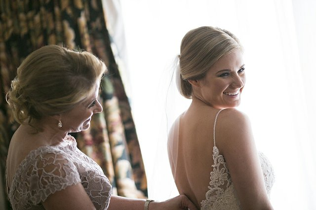 Mother of the bride making adjustments to daughter's wedding dress