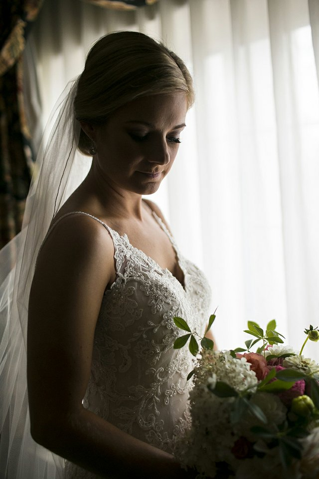 Bride posing with bouquet near window with dramatic lighting