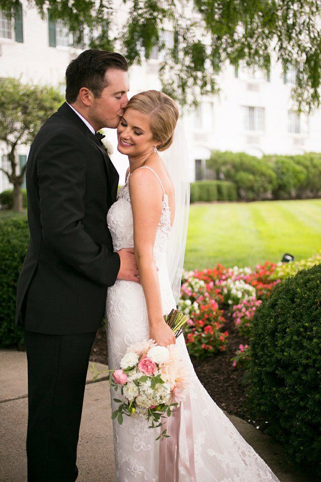 Groom kissing bride's forehead in front of historic hotel