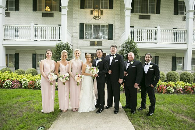 Bridal party posing in front of historic hotel with white bricks, black shutters, colonnade and manicured garden