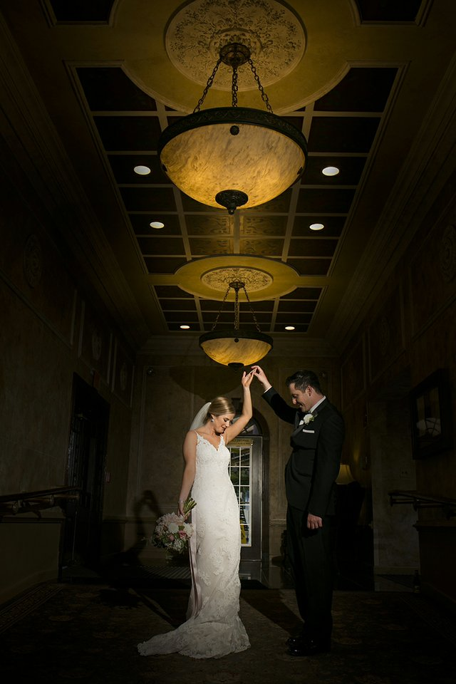 Bride and groom making their entrance in a hotel hallway with dramatic lighting