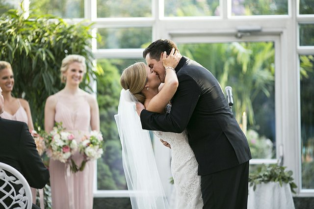 Bride and groom sharing a passionate kiss on the dancefloor at their wedding reception
