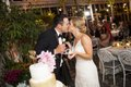 Bride and groom kissing after cutting wedding cake