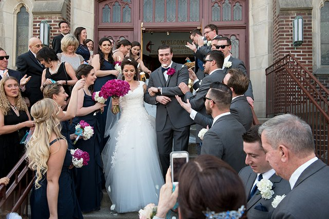 Crowd shot of bride and groom processing out the front steps of a church, surrounded by friends and family