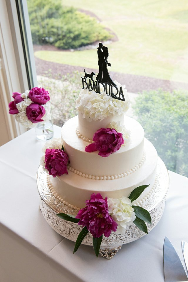 White tiered wedding cake with pearl icing and magenta floral details