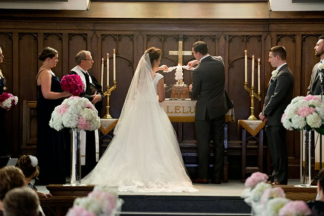 Bride and groom lighting candle on altar during wedding ceremony