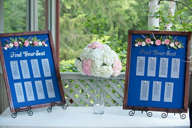Wedding seating chart featuring small table lists affixed to wooden frames with floral details