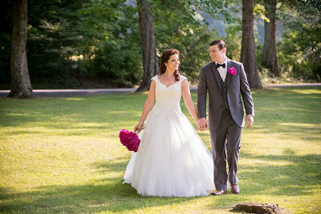Bride and groom walking hand-in-hand in a grassy field