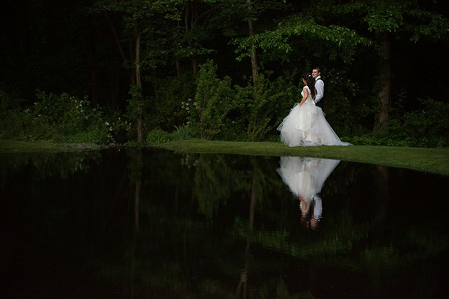 Dramatic nighttime shot of bride and groom strolling near a pond, reflected in the still water