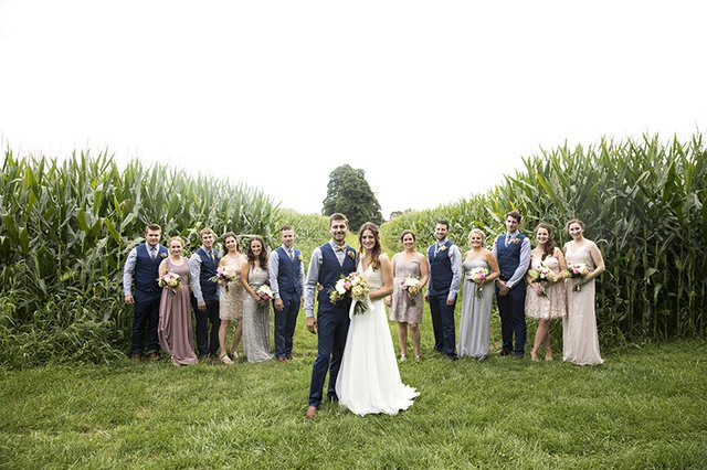 Group photo of bridal party in corn field