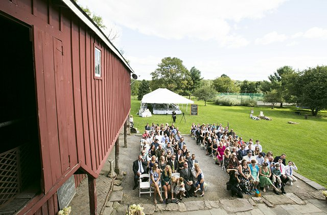 High angle crowd photo of seated guests at outdoor barn wedding