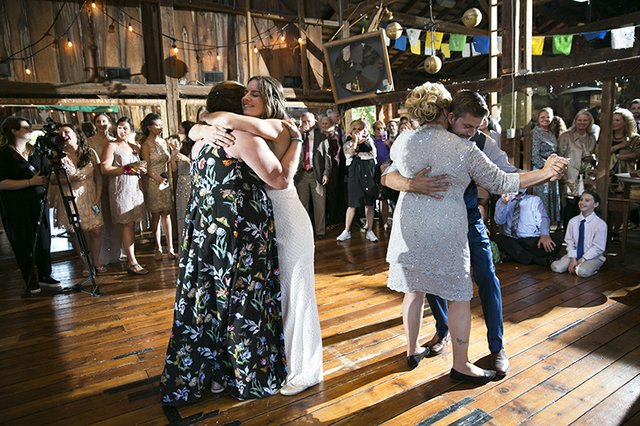 Bride and groom dancing with parents at wedding reception