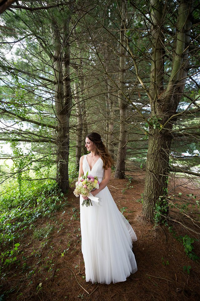 Bride posing with bouquet of flowers in copse of evergreen trees