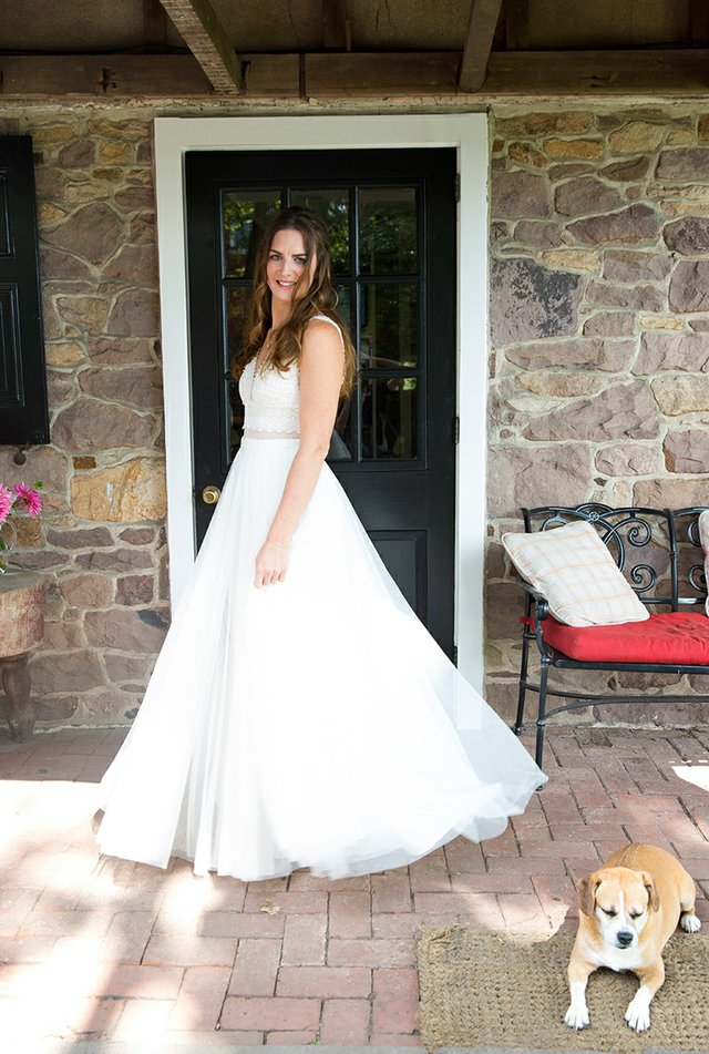 Bride in wedding dress posing in front of fieldstone wall with dog
