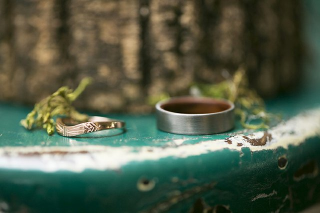 Depth of field photo of custom wedding bands on distressed table with greenery