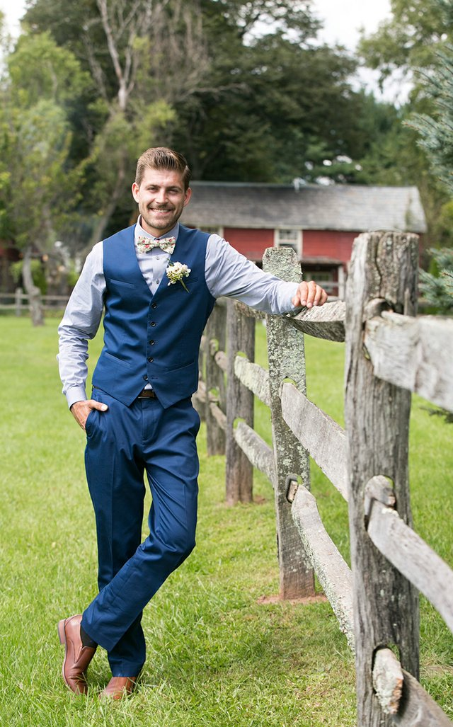 Groom in blue vest and floral bowtie leaning on split-rail fence