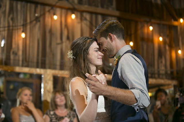 Bride and groom sharing first dance at barn wedding