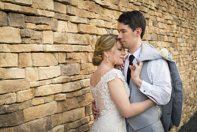 Bride and groom in white lace dress and grey summer linen suit posing near stone wall