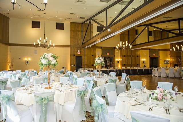 Wedding reception hall with white table linens and sea green accents