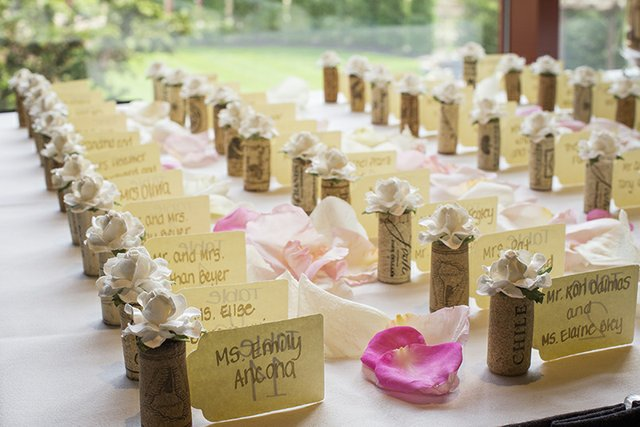 Wedding reception table cards featuring wine corks and flower petals