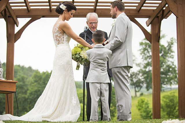 Bride and groom exchanging vows at outdoor wedding ceremony with pergola