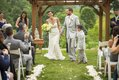 Bride, groom and child recessing at outdoor wedding ceremony with pergola