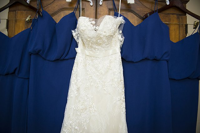 White lace bridal gown and wedding dresses arranged on hangars
