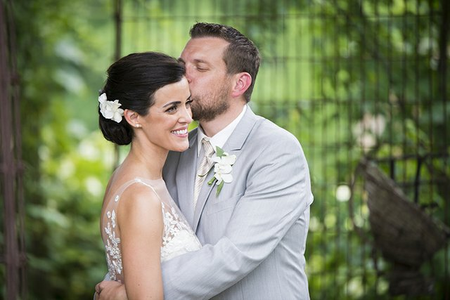 Groom tenderly kissing bride's forehead, posing outdoors with greenery behind