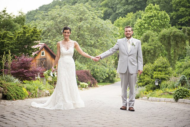 Bride and groom posing outdoors, standing hand-in-hand, white lace dress and light grey summerweight suit