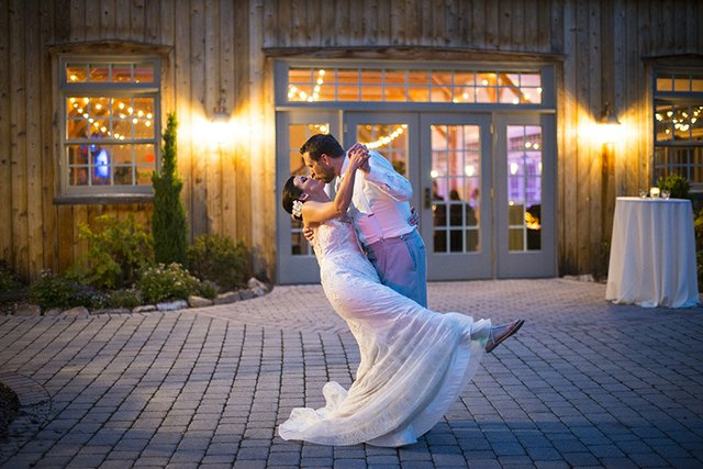 Groom dipping bride, sharing kiss in evening on stone patio outside of venue