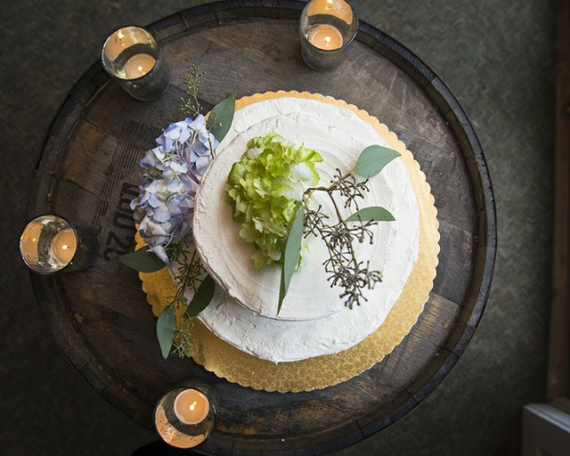 Top-down shot of tiered wedding cake with floral decoration arranged on wooden cask with tea lights