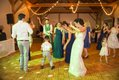 Bridal party dancing with small children on parquet floor at wedding reception