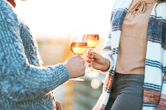 Young couple in autumn vineyard toasting with rosé wine.