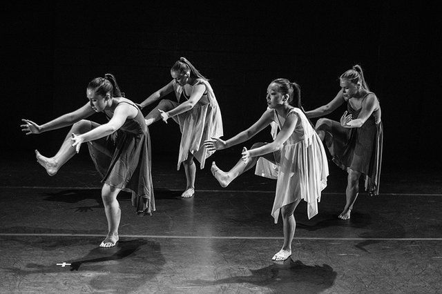 Black and white image of four choreographed modern dancers performing on stage. Photo by Ketan Rajput on Unsplash.