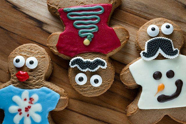 Gingerbread cookies with googly eyes, wearing ugly Christmas sweaters made from frosting.